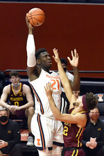 Illinois center Kofi Cockburn (21) puts the ball up as Minnesota's guard Gabe Kalscheur (22) defends in the first half of an NCAA college basketball game Tuesday, Dec. 15, 2020, in Champaign, Ill. (AP Photo/Holly Hart)