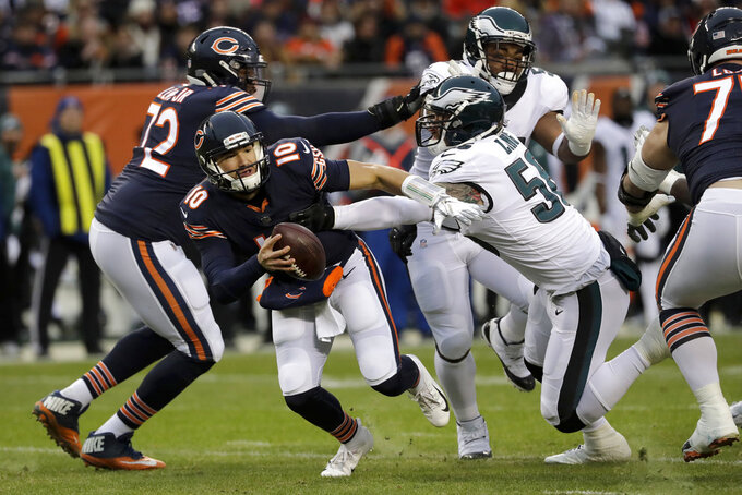 Chicago Bears quarterback Mitchell Trubisky (10) runs away from Philadelphia Eagles defensive end Chris Long (56) during the first half of an NFL wild-card playoff football game Sunday, Jan. 6, 2019, in Chicago. (AP Photo/Nam Y. Huh)