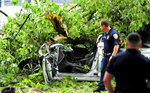 In this Wednesday, July 17, 2019 photo, police officers look on after emergency personnel  removed a victim from a crushed car after a tree fell on the vehicle along Park Ave. in Bridgeport, Conn, Firefighters had to wait nearly an hour for an electrical crew to shut down power to the wires before they could remove 21-year-old Jarrod Marotto. A series of powerful thunderstorms was moving through the area at the time. (Christian Abraham/Hearst Connecticut Media via AP)