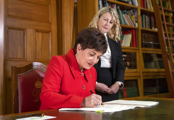 New Zealand Governor General Patsy Reddy, left, assisted by the Deputy Clerk of the House, Suze Jones, at Government House in Wellington, Thursday, April 11, 2019, signs into effect sweeping gun laws outlawing military-style weapons, less than a month after a man used such guns to kill 50 people and wounded dozens at two mosques in Christchurch. (Mark Mitchell/New Zealand Herald via AP)