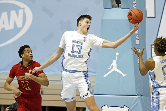 FILE - Then-North Carolina forward Walker Kessler (13) grabs a rebound over Louisville forward JJ Traynor (12) while North Carolina guard Anthony Harris (0) reaches in during the first half of an NCAA college basketball game in Chapel Hill, N.C., in this Saturday, Feb. 20, 2021, file photo. Bruce Pearl has rebuilt Auburn's roster once again, only this time with expectations for immediate success. The preseason No. 22 Tigers' coach restocked his team with talented transfers like North Carolina 7-footer Walker Kessler, Georgia guard K.D. Johnson and five-star recruit Jabari Smith after a down year that followed the program's best three-year run in history. (AP Photo/Gerry Broome, File)