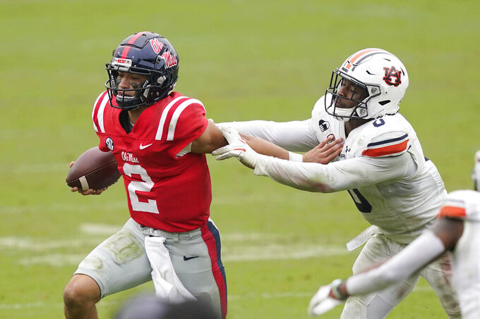Mississippi quarterback Matt Corral (2) evades a tackle by Auburn linebacker Owen Pappoe (0) during the second half of an NCAA college football game in Oxford, Miss., Saturday Oct. 24, 2020. (AP Photo/Rogelio V. Solis)