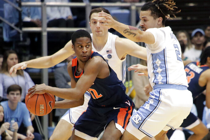 Virginia's Chase Coleman (12) is defended by North Carolina's Justin Pierce (32) and Cole Anthony (2) during the first half of an NCAA college basketball game at the Dean Smith Center in Chapel Hill, N.C., Saturday, Feb. 15, 2020. (AP Photo/Chris Seward)