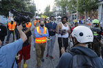 Seattle Department of Transportation workers walk and talk with protest organizers near the Seattle Police Department East Precinct building after SDOT arrived at the the CHOP (Capitol Hill Occupied Protest) zone in Seattle, Friday, June 26, 2020, with the intention of removing barricades that had been set up in the area. Several blocks in the area have been occupied by protesters since Seattle Police pulled back from their East Precinct building following violent clashes with demonstrators earlier in the month. (AP Photo/Ted S. Warren)