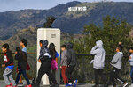In this Friday, Jan. 17, 2020, photo, school children walk past a bust of actor James Dean during a field trip, at the Griffith Observatory in the Griffith Park area of Los Angeles. Travis Cloyd, who is leading the revival of Dean for his appearance in