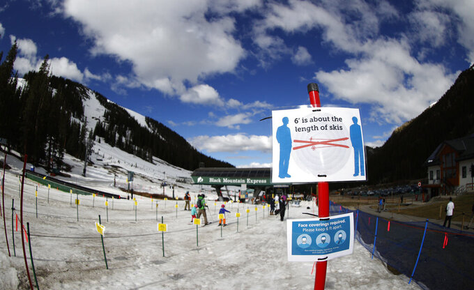 FILE - In this May 27, 2020, file photo, signs stand at the lines to the lift at the reopening of Arapahoe Basin Ski Resort, which closed in mid-March to help in the effort to stop the spread of the new coronavirus, in Keystone, Colo. Colorado health officials are weighing in on how to safely navigate the upcoming ski season amid a pandemic as eager skiers and snowboarders who have been cooped up for the greater part of a year prepare to hit the slopes in a matter of weeks. The Colorado Department of Public Health & Environment released its final guidance Monday, Oct. 19, after gathering feedback from resorts and county health officials. (AP Photo/David Zalubowski, File)