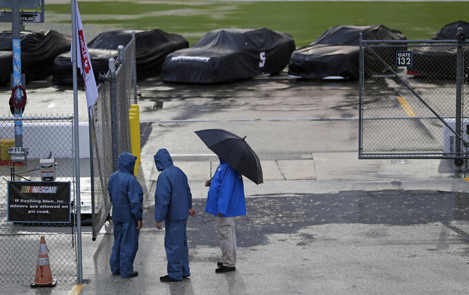 Races cars sit covered and idle on pit road as track workers gather nearby during a rain storm delaying a NASCAR Xfinity Series auto race at Daytona International Speedway, Friday, July 5, 2019, in Daytona Beach, Fla. (AP Photo/John Raoux)
