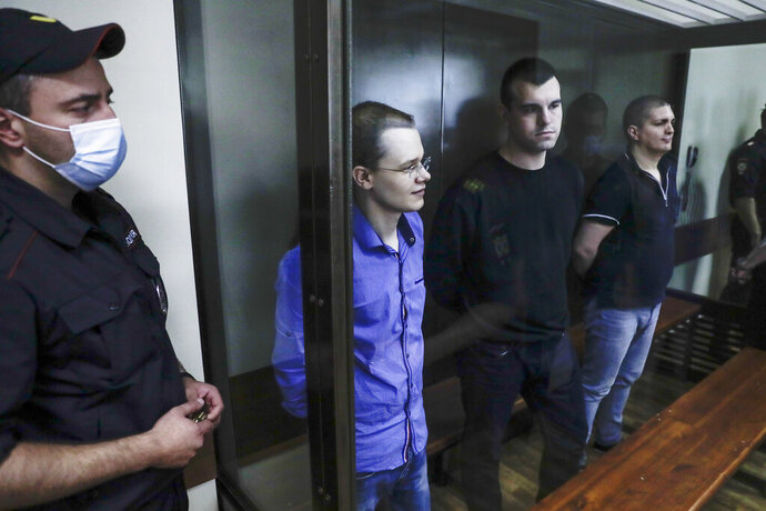 Members of the New Greatness group, who are charged with the organization of an extremist association, stand behind a glass in a courtroom prior a hearing in Moscow, Russia, Thursday, Aug. 6, 2020. Arrests of the two youngest members of the New Greatness group - 17-year-old Anna Pavlikova and 19-year-old Maria Dubovik - prompted a mass protest in August 2018, after which the two teenagers were released under house arrest. (AP Photo/Pavel Golovkin)