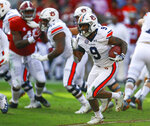 FILE - In this Saturday, Nov. 24, 2018 file photo, Auburn running back Kam Martin (9) carries the ball against Alabama during the first half of an NCAA college football game in Tuscaloosa, Ala. College football starts better than it ends. The sport has evolved through numerous postseason systems that have clumsily crowned champions, and while the College Football Playoff does a better job than its predecessors it has also spawned a month's worth of tedious debate over the meaningfulness of bowl games. (AP Photo/Butch Dill, File)
