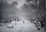 A pedestrian crosses the street as a major winter storm brings heavy snow in Ottawa on Saturday, Jan. 16, 2021.   (Justin Tang/The Canadian Press via AP)