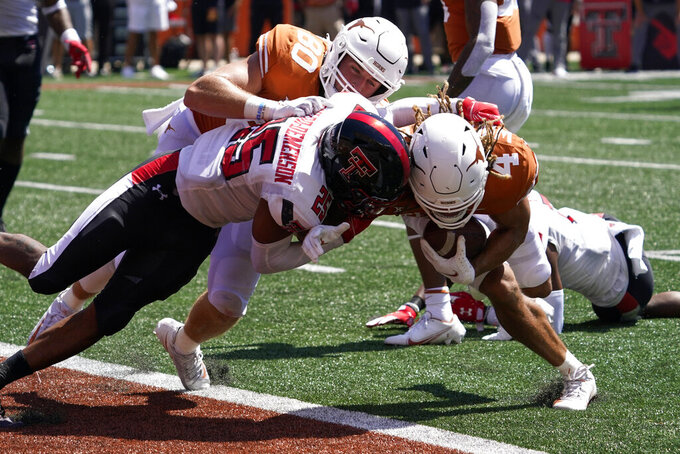 Texas wide receiver Jordan Whittington (4) runs into the end zone for a touchdown against Texas Tech defensive back Dadrion Taylor-Demerson (25) during the second half of an NCAA college football game on Saturday, Sept. 25, 2021, in Austin, Texas. (AP Photo/Chuck Burton)