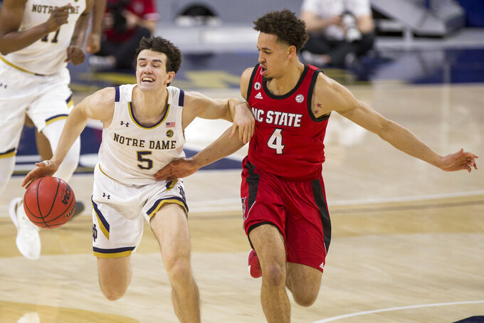 Notre Dame's Cormac Ryan (5) drives downcourt with pressure from North Carolina State's Jericole Hellems (4) during the second half of an NCAA college basketball game Wednesday, March 3, 2021, in South Bend, Ind. North Carolina State won 80-69. (AP Photo/Robert Franklin)