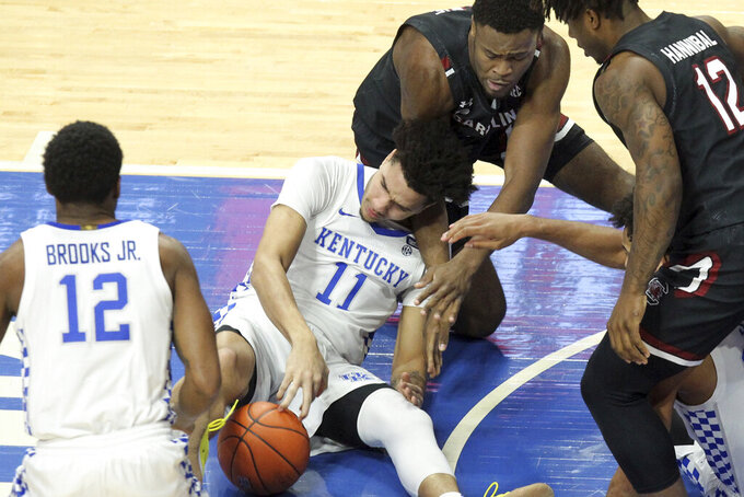 South Carolina's Wildens Leveque, right, and Kentucky's Dontaie Allen (11) try to gain control of the ball as Keion Brooks Jr. looks on during the first half of an NCAA college basketball game in Lexington, Ky., Saturday, March 6, 2021. (AP Photo/James Crisp)