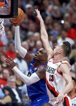 Denver Nuggets forward Paul Millsap, left, shoots over Portland Trail Blazers forward Zach Collins during the first half of Game 3 of an NBA basketball second-round playoff series Friday, May 3, 2019, in Portland, Ore. (AP Photo/Craig Mitchelldyer)