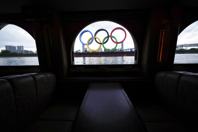 FILE - In this April 12, 2021, file photo, the Olympic rings floating in the water in the Odaiba section are seen from a window of a water bus, in Tokyo. Public sentiment in Japan has been generally opposed to holding the Tokyo Olympics and Paralympics. This is partly based of fears the coronavirus will spike as almost 100,000 people — athletes and others — enter for both events.(AP Photo/Eugene Hoshiko, File)