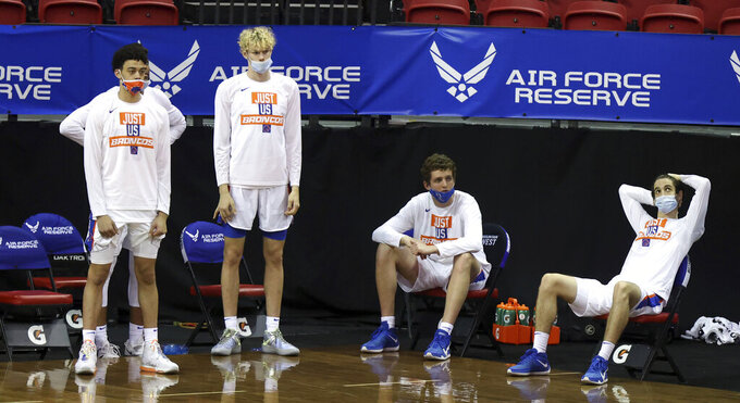 Players on the Boise State bench watch during the final minutes of the team's NCAA college basketball game against Nevada in the quarterfinals of the Mountain West Conference men's tournament Thursday, March 11, 2021, in Las Vegas. (AP Photo/Isaac Brekken)