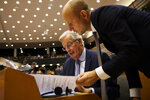 European Union chief Brexit negotiator Michel Barnier, left, talks to his assistant before addressing European lawmakers at the European Parliament in Brussels, Wednesday, Oct. 9, 2019. (AP Photo/Francisco Seco)