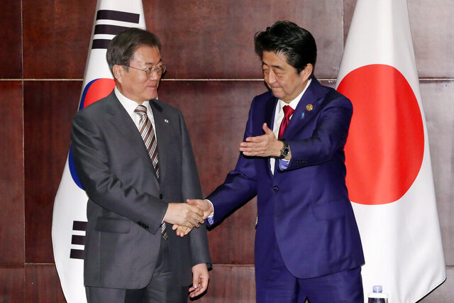 South Korean President Moon Jae-in, left, shakes hands wth Japanese Prime Minister Shinzo Abe during a meeting in Chengdu, China, Tuesday, Dec. 24, 2019. (Lee Jin-wook/Yonhap via AP)