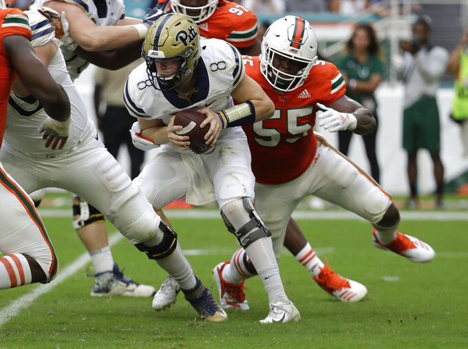 Pittsburgh quarterback Kenny Pickett (8) is tackled by Miami linebacker Shaquille Quarterman (55) during the first half of an NCAA college football game, Saturday, Nov. 24, 2018, in Miami Gardens, Fla. (AP Photo/Lynne Sladky)