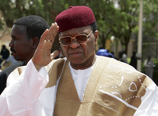 FILE - In this Friday, March 27, 2009, file photo, Niger President Mamadou Tandja waves upon his arrival to welcome French President Nicolas Sarkozy at Diori Hamani airport in Niamey, Niger. Former Niger President Mamadou Tandja died Tuesday, Nov. 24, 2020, at age 82, according to the government. (AP Photo/Francois Mori, Pool, File)