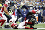 Seattle Seahawks running back Chris Carson (32) is tackled by Arizona Cardinals linebacker Chandler Jones (55) above Cardinals strong safety Budda Baker, lower left, during the first half of an NFL football game, Sunday, Dec. 22, 2019, in Seattle. (AP Photo/Lindsey Wasson)