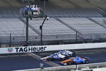 Takuma Sato, middle, of Japan, crosses the start/finish line to win the Indianapolis 500 auto race at Indianapolis Motor Speedway, Sunday, Aug. 23, 2020, in Indianapolis. Scott Dixon, front, of New Zealand, finished second and Graham Rahal, back, finished third. (AP Photo/Darron Cummings)