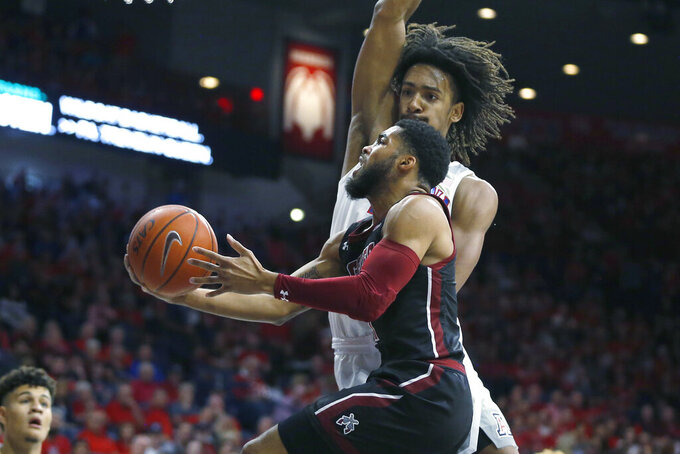 New Mexico State guard Shunn Buchanan drives past Arizona forward Zeke Nnaji (22) in the first half during an NCAA college basketball game, Sunday, Nov. 17, 2019, in Tucson, Ariz. (AP Photo/Rick Scuteri)