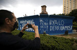 FILE - In this Oct. 12, 2020 file photo, a pedestrian takes a photo of graffiti that reads in Spanish