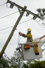 A lineman works to restore power in Gloster, Miss., on Saturday, Oct. 10, 2020, after Hurricane Delta struck parts of Mississippi overnight. (Matt Williamson/The Enterprise-Journal via AP)