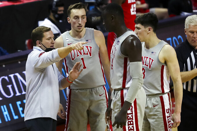 UNLV head coach T.J. Otzelberger gives directions to forwards Moses Wood (1), Cheikh Mbacke Diong (34) and guard Caleb Grill (3) during an NCAA college basketball game against New Mexico, Monday, Jan. 18, 2021, in Las Vegas. (Wade Vandervort/Las Vegas Sun via AP)