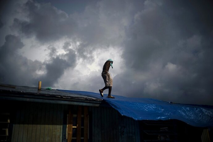 Trevon Laing walks the roof of his house to repair the damage made by Hurricane Dorian, in Gold Rock Creek, Grand Bahama, Bahamas, Thursday Sept. 12, 2019. Trevor says