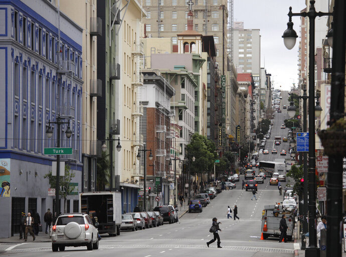 In this Feb. 15, 2011, file photo, shown is a view looking up Taylor Street of the Tenderloin neighborhood in San Francisco. Seventeen federal law enforcement agencies are teaming up for a year-long crackdown on a notorious area of San Francisco where open drug use has been tolerated for years. U.S. Attorney David Anderson said Wednesday, Aug. 7, 2019, that the federal government is targeting the city's Tenderloin neighborhood with arrests of drug traffickers as the first step in cleaning up a roughly 50-block area he says is