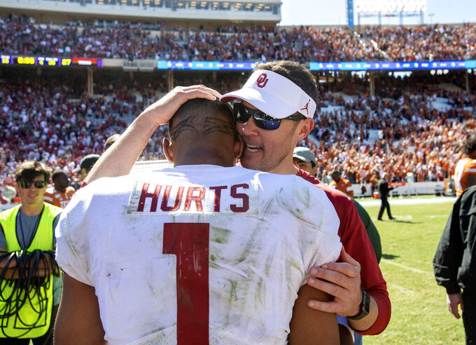Oklahoma head coach Lincoln Riley congratulates quarterback Jalen Hurts (1) after beating Texas 34-27 in an NCAA college football game at the Cotton Bowl, Saturday, Oct. 12, 2019, in Dallas. (AP Photo/Jeffrey McWhorter)