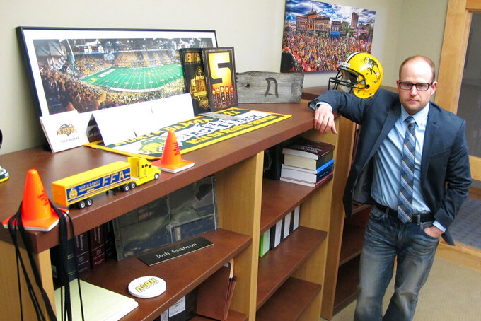 FILE - In this March 18, 2016, file photo, Fargo attorney Josh Swanson, of the Vogel Law Firm in Fargo, N.D., poses in his office next to a bookcase that contains numerous items of memorabilia from his alma mater North Dakota State University. NDSU seems to have perfected the art of reloading. The Bison are 12-0 and the top seed again in the FCS playoffs despite breaking in a new coach and a new quarterback this season. But with all their winning, seven of the last eight championships, is it all starting to get a little routine in Fargo? (AP Photo/Dave Kolpack, File)