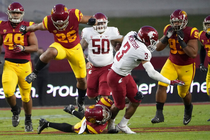 Washington State running back Deon McIntosh (3) is brought down by Southern California safety Isaiah Pola-Mao, below center, as linebacker Kana'i Mauga (26) leaps over to avoid Pola-Mao during the first half of an NCAA college football game in Los Angeles, Sunday, Dec. 6, 2020. (AP Photo/Alex Gallardo)