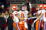 Clemson's Trevor Lawrence (16) congratulates Travis Etienne (9) on his touchdown during the second half of an NCAA college football game against North Carolina State in Raleigh, N.C., Saturday, Nov. 9, 2019. (AP Photo/Karl B DeBlaker)