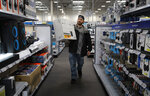 FILE - In this Nov. 26, 2019, file photo Nick Bierman carries an an audio system while shopping ahead of Black Friday at a Best Buy in Henderson, Nev. Best Buy reports earnings Thursday, Feb. 27. (AP Photo/John Locher, File)