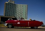 A vintage American car carries tourists next to hotel Riviera, managed by the Spanish company Iberostar, in Havana, Cuba, Wednesday, April 24, 2019. The European Union ambassador to Cuba says the Trump administration's crackdown on business with the communist government is causing unprecedented concern among European companies doing business on the island. (AP Photo/Ramon Espinosa)