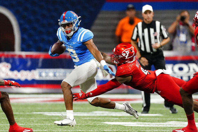 Mississippi running back Jerrion Ealy (9) tries to escape from Louisville linebacker C.J. Avery (9) during the first half of an NCAA college football game Monday, Sept. 6, 2021, in Atlanta. (AP Photo/John Bazemore)
