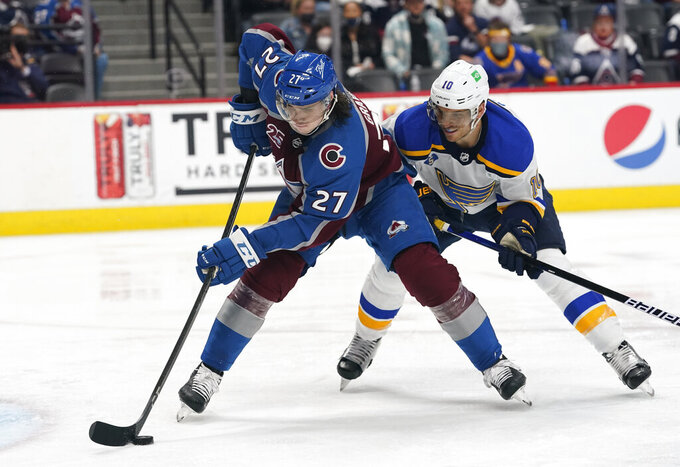 FILE - In this May 19, 2021, file photo, Colorado Avalanche defenseman Ryan Graves (27) works with the puck in front of St. Louis Blues center Brayden Schenn (10) during Game 2 of an NHL hockey Stanley Cup first-round playoff series in Denver. The Avalanche sent Graves to the New Jersey Devils in a move made with an eye on the upcoming expansion draft of the Seattle Kraken. In exchange, the Avalanche acquired forward Mikhail Maltsev and a second-round selection in the 2021 draft from New Jersey. (AP Photo/David Zalubowski, File)