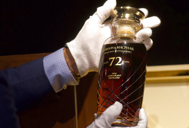 Expecting to fetch more than US$49,000 at auction, a 72-year-old bottle of Glen Grant single malt whisky from Scotland is displayed at a Bonhams auction preview in Hong Kong, Thursday, Jan. 28, 2021. Despite the economic uncertainty brought on by the pandemic, interest in the rare whisky remains high. Compared to other investment commodities, collectable whisky is doing strong in the past 10 years, with a four-fold increase in its price, Bonhams specialist Christopher Pong said. (AP Photo/Vincent Yu)