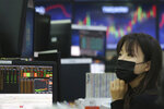 A currency trader wearing a face mask watches monitors at the foreign exchange dealing room of the KEB Hana Bank headquarters in Seoul, South Korea, Friday, Feb. 21, 2020. Asian stock markets have followed Wall Street lower after a rise in virus cases in South Korea refueled investor anxiety about China's disease outbreak. (AP Photo/Ahn Young-joon)