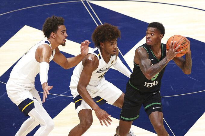 North Texas guard Javion Hamlet (3) looks to pass the ball while defended by West Virginia forward Emmitt Matthews Jr., left, and guard Miles McBride (4) during the second half of an NCAA college basketball game Friday, Dec. 11, 2020, in Morgantown, W.Va. (AP Photo/Kathleen Batten)