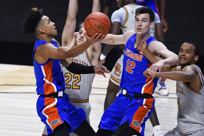 Florida's Tre Mann makes a basket against Boston College's Rich Kelly, second from right as Florida's Colin Castleton and Boston College's Steffon Mitchell, right, watch during the first half of an NCAA college basketball game, Thursday, Dec. 3, 2020, in Uncasville, Conn. (AP Photo/Jessica Hill)
