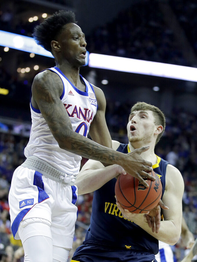 Kansas' Marcus Garrett (0) tries to steal the ball from West Virginia's Logan Routt during the first half of an NCAA college basketball game in the Big 12 men's tournament Friday, March 15, 2019, in Kansas City, Mo. (AP Photo/Charlie Riedel)