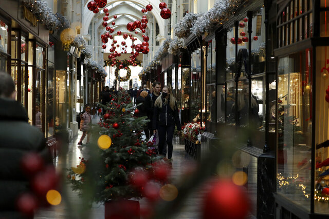 People walk past Christmas trees and decorations in the Burlington Arcade as shops are allowed to stay open under the British government's coronavirus Tier system, in London, Thursday, Dec. 17, 2020. London and its surrounding areas came under Tier 3 restrictions this Wednesday, with the latest figures showing the capital now has among the fastest growing case rates in the country. Tier 3 restrictions are the toughest level in England's three-tier system, people can't socialize indoors, and bars, pubs and restaurants must close except for takeout. (AP Photo/Matt Dunham)