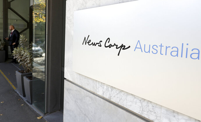A security guard stands at the entrance to the News Corp. headquarters in Sydney, Thursday, May 28, 2020. Australia's largest newspaper publisher, News Corp., announced that most of its suburban and regional mastheads across the country will become digital-only next month due to the pandemic and digital platforms sharing their content. (AP Photo/Rick Rycroft)