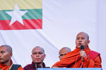 In this May 5, 2019, photo, Buddhist monk and anti-Muslim community leader Wirathu, right, speaks during a nationalist rally in Yangon, Myanmar. A court issued Wednesday, May 29, 2019, an arrest warrant for the Buddhist monk famous for his incendiary comments about the country's Muslim minority and criticisms of the government. The warrant issued in Yangon charges Wirathu with sedition for remarks he made on May 5 about the government of Myanmar's leader, Aung San Suu Kyi. (AP Photo/Aung Naing Soe)