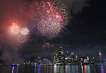 A surprise display of fireworks sponsored by Macy's explode over the Hudson Yards area of Manhattan as seen from a pier in Hoboken, N.J., late Tuesday, June 30, 2020. Coronavirus concerns are changing the way the holiday is celebrated. In New York, the Macy's annual summer spectacle was replaced by a series of smaller, surprise shows. They've been ringing out all week, leading into the televised finale Saturday.  (AP Photo/Kathy Willens)
