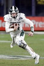 Michigan State quarterback Brian Lewerke (14) rushes during the second half of the Pinstripe Bowl NCAA college football game against Wake Forest, Friday, Dec. 27, 2019, in New York. (AP Photo/Frank Franklin II)